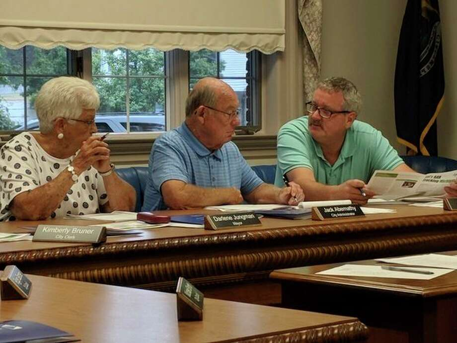 Gladwin Mayor Dee Jungman, from left, interim city manager Jack Abernathy and mayor pro-tem John Caffrey, discuss hiring the Michigan Municipal League during Monday's city council meeting. The council voted 5-2 to hire the MML for $15,500. (Tereasa Nims/for the Daily News)