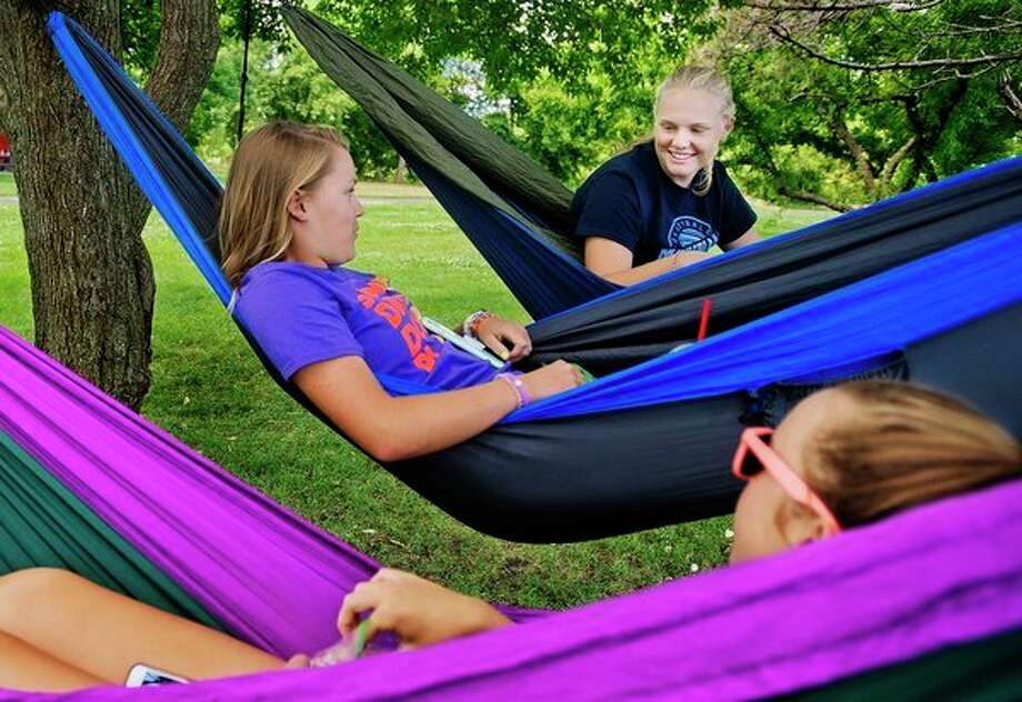 Sanford residents Makayla Kent, 17, top, Allison Sutton, 15, center, and Brooklyn Kelly, 17, bottom, chat while relaxing in hammocks near the Tridge on Tuesday afternoon. (Katy Kildee/kkildee@mdn.net)