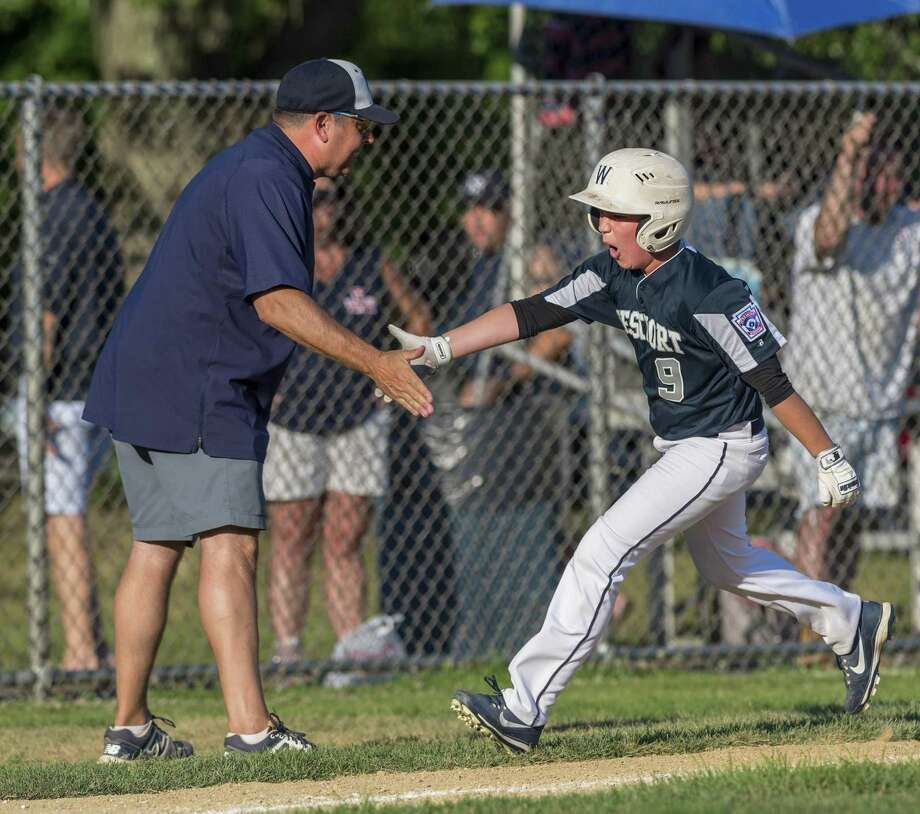 Westport manager Jim Farnen congratulates his son after Jack hit a home run against Fairfield National in the District 2 Little League tournament at Unity Park. Photo: Mark Conrad / For Hearst Connecticut Media / Connecticut Post Freelance