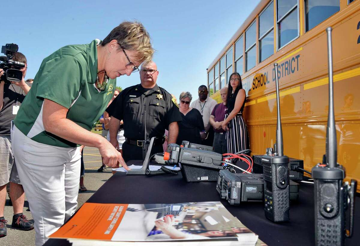 Ravena Coeymans Selkirk Schools' Joanne Moran tests a new two-way radio with panic button as part of a multifaceted strategy to promote school safety at a news conference at Ravena Coeymans Selkirk High School Wednesday July 18, 2018 in Ravena, NY. (John Carl D'Annibale/Times Union)