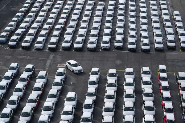 A newly manufactured Audi is driven into a parking space as Volkswagen brand vehicles stand ahead of shipping outside the VW factory at the port in Emden, Germany, on March 9, 2018.
