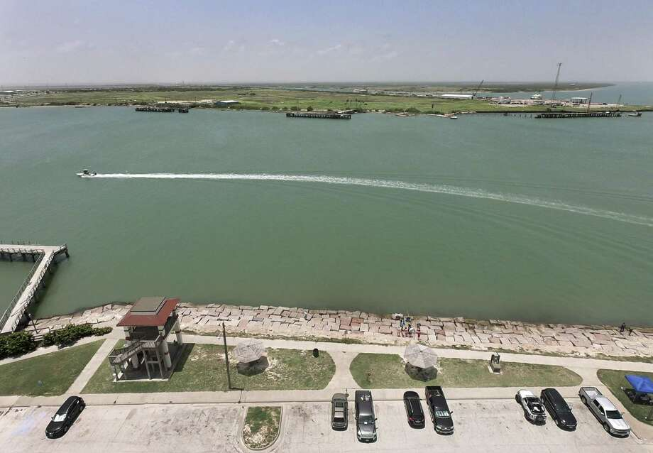 A boat traverses the waters between Port Aransas, foreground, and Harbor Island, in the distance, on Friday, June 29, 2018. Harbor Island is the site of a 250-acre crude oil terminal proposed by the Port of Corpus Christi. It was once the site of an Exxon terminal. Photo: Billy Calzada, Staff / San Antonio Express-News / San Antonio Express-News