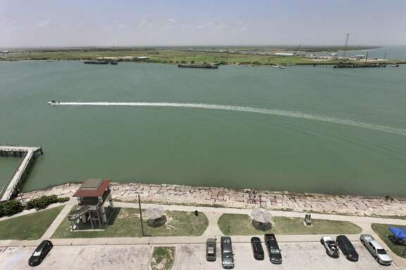A boat traverses the waters between Port Aransas, foreground, and Harbor Island, in the distance, on Friday, June 29, 2018. Harbor Island is the site of a crude oil export terminal proposed by the Port of Corpus Christi. It was once the site of an Exxon terminal.