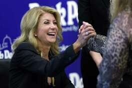 In this Sept. 11, 2014 photo, Texas Democratic gubernatorial candidate Wendy Davis visits with supporters at a book signing in Austin, Texas. Davis is expected to lose the Texas governorâ??s race, but that could be a long-term win for Democrats. The state senator from Fort Worth has shattered fundraising records, breathed life into a Texas Democratic Party mired in the nationâ??s longest political losing streak and stepped up to run in a race that looks unwinnable, buying time to groom a political bench that could face easier future elections. (AP Photo/Eric Gay)
