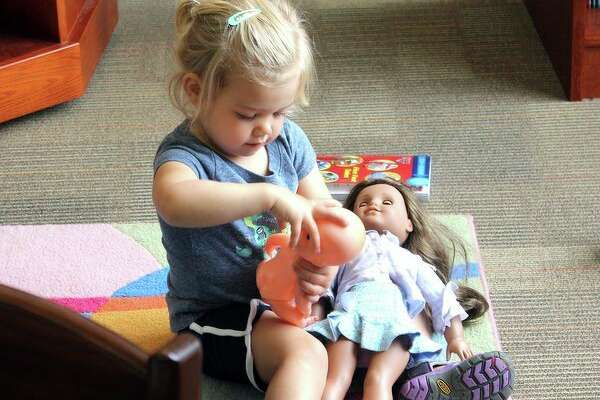 June Hofmeister, 2, plays with her baby doll and an America Girl Doll at the Port Austin Township Library. The American Girl Dolls are available for checkout at the library. (Brenda Battel/Huron Daily Tribune)