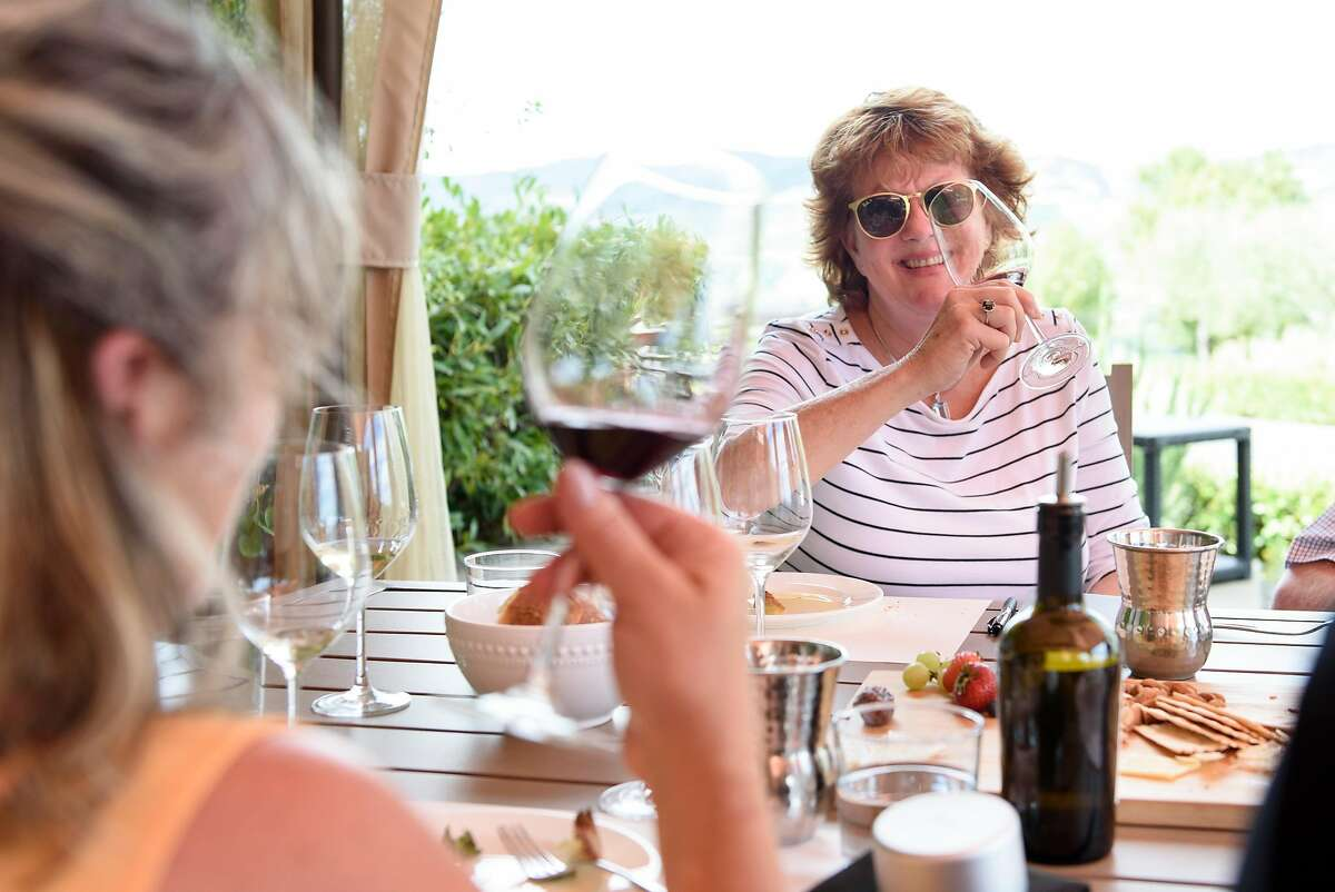 Guests Jorie Sanders, right, and Rachel Harris taste wine on the patio at Antica Winery in Napa, Calif., on Friday July 6, 2018.