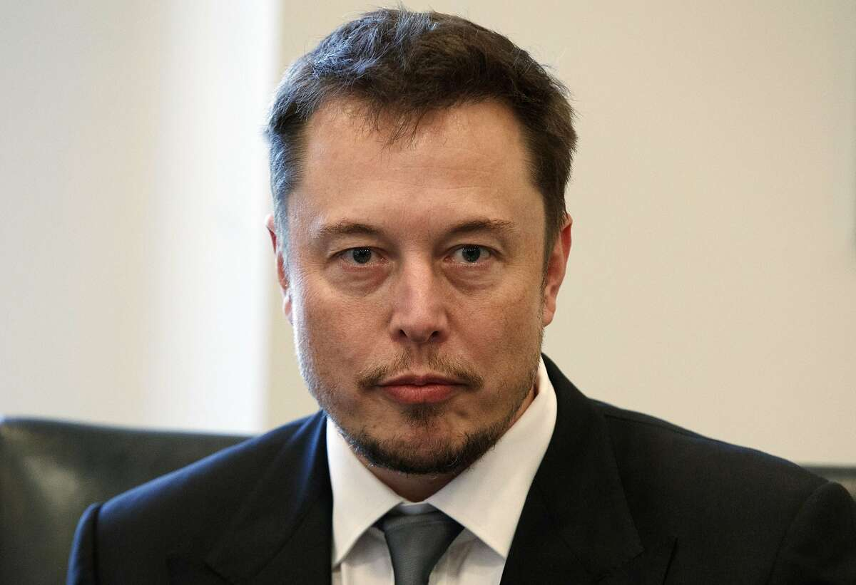 FILE - In this Dec. 14, 2016, file photo, Tesla CEO Elon Musk listens as President-elect Donald Trump speaks during a meeting with technology industry leaders at Trump Tower in New York.