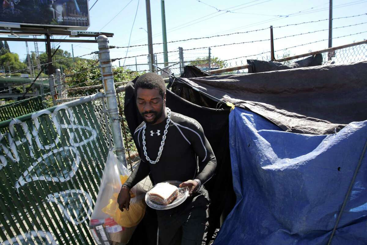 Jerry, 37, who has been homeless on and off for years, emerges from his makeshift tent near the Navigation Center in the Central District. Jerry spent a few weeks living at the Center and said it was helpful to him but he was temporarily kicked out. He says the most difficult part about being homeless is not having anywhere to keep your belongings safe and secure.