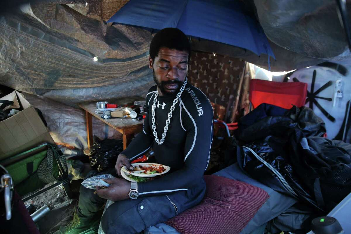 Jerry, 37, who has been homeless on and off years, sits in his makeshift tent near the Navigation Center in the Central District. Jerry spent a few weeks living at the Center and said it was helpful to him but he was temporarily kicked out. He says the most difficult part about being homeless is not having anywhere to keep your belongings safe and secure.