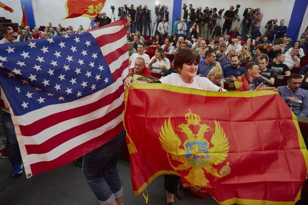 Supporters of Democratic Socialist Party leader Milo Dukanovic wave Montenegrin and U.S. flags after victory in the presidential election on April 15, 2018 in Podgorica, Montenegro.