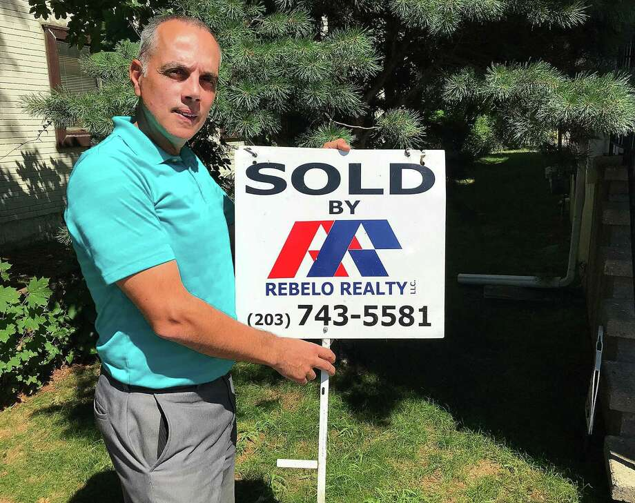 David Vieira, owner of Rebelo Realty, holds one of his sold signs near his office on White Street in Danbury, Conn., on Wednesday, July 18, 2018. Photo: Chris Bosak / Hearst Connecticut Media / The News-Times