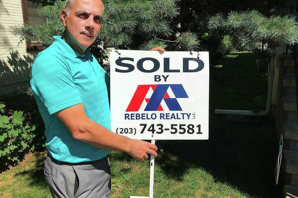 David Vieira, owner of Rebelo Realty, holds one of his sold signs near his office on White Street in Danbury, Conn., on Wednesday, July 18, 2018.