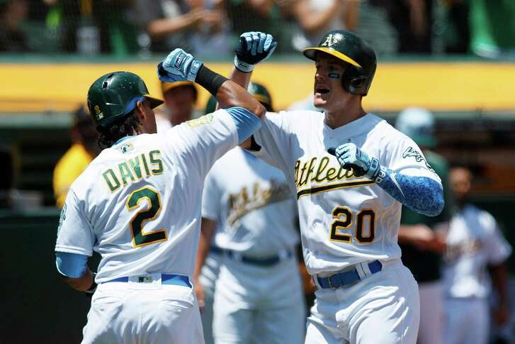 Mark Canha #20 of the Oakland Athletics is congratulated by Khris Davis #2 after hitting a two run home run against the Los Angeles Angels of Anaheim during the second inning at the Oakland Coliseum on June 17, 2018 in Oakland, California. (Photo by Jason O. Watson/Getty Images)