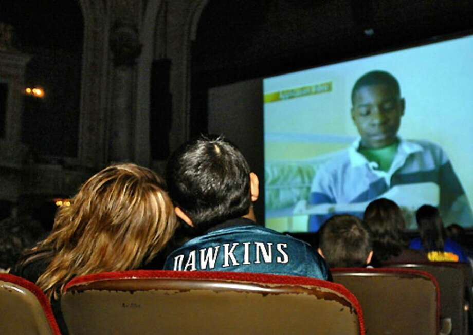 Debbie Oatman-Gaitan leans her head on her son Scout's shoulder while watching the 'Extreme Makeover' episode at Proctor's Theatre in Schenectady on Sunday. Photo: Philip Kamrass