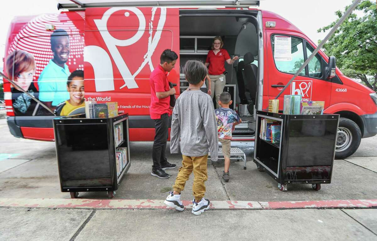 Luis Cerna and Rachel Stout welcome Second Ward and area children to enter the Houston Public Library Bookmobile Thursday, July 5, 2018, in Houston. The Flores Neighborhood Library is one of six Houston Public Library branches that has been closed since Harvey damaged it last August. ( Steve Gonzales / Houston Chronicle )