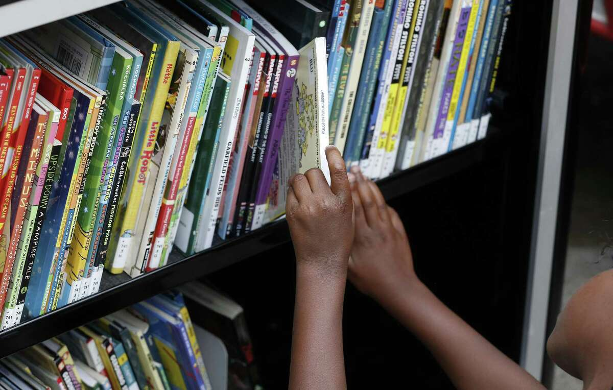 Second Ward and area children look though books at the Houston Public Library Bookmobile Thursday, July 5, 2018, in Houston. The Flores Neighborhood Library is one of six Houston Public Library branches that has been closed since Harvey damaged it last August. ( Steve Gonzales / Houston Chronicle )