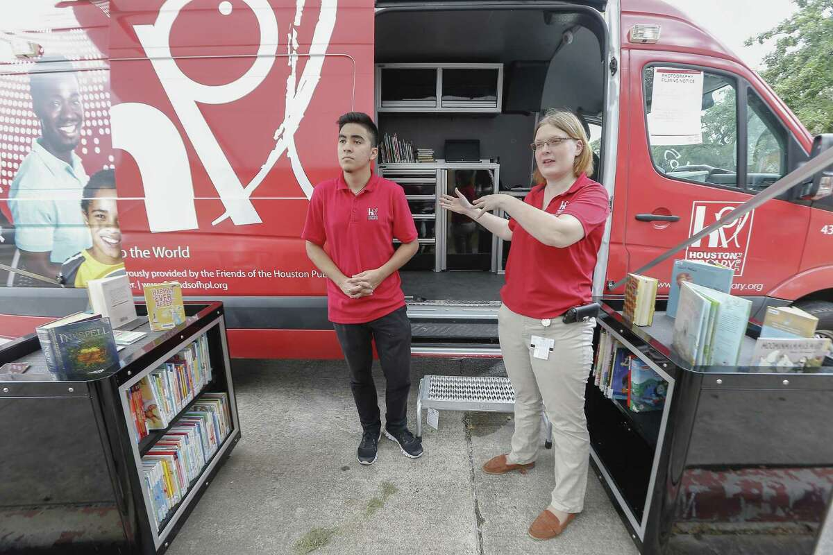 Luis Cerna and Rachel Stout brought the Houston Public Library Bookmobile to Second Ward and area children Thursday, July 5, 2018, in Houston. The Flores Neighborhood Library is one of six Houston Public Library branches that has been closed since Harvey damaged it last August. ( Steve Gonzales / Houston Chronicle )