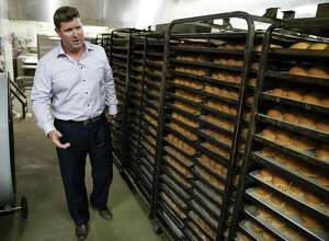 Bill Miller Bar-B-Q CEO Jim Guy Egbert inspects bakery cooling racksat the Bill Miller commissary in Downtown San Antonio.