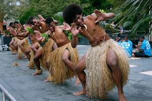 """Jope Kalou (right) and other Fijian dancers perform a """"meke"""" dance at Union Square in San Francisco, Calif. on Tuesday, July 17, 2018. The performances by the Kabu ni Vanua dancers are ahead of the Fiji rugby seven team's appearance in the Rugby World Cup Sevens tournament this weekend at AT&T Park."""