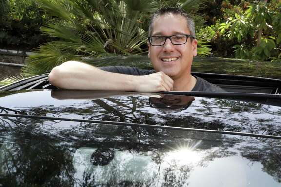 Keith Reynolds, who is on the Tesla waiting list for a Model 3, is photographed by his 9-year-old Audi A3 compact car Monday, July 16, 2018, in Laguna Hills, Calif. For many on the list to buy Tesla's mass-market electric car, the wait for the company to produce enough to satisfy demand isn't a major problem. But the prospect of losing a U.S. federal tax credit is.