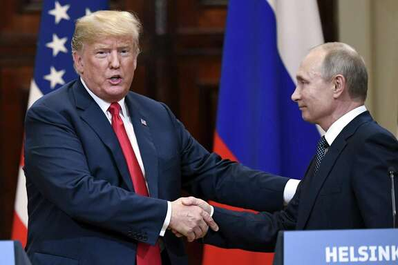 U.S. President Donald Trump and Russian President Vladimir Putin shake hands after a joint press conference at the Presidential Palace in Helsinki, Finland on Monday. It was Trump channeling Neville Chamberlain, except without the umbrella.