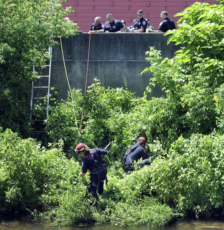Firefighters search the banks of the Still River off Crosby Street, for a baby that may have been thrown in, Monday, July 18, 2018. Photo: Carol Kaliff / Hearst Connecticut Media / The News-Times