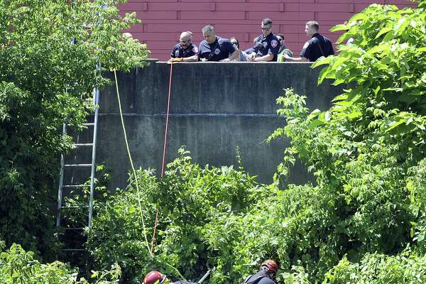 Firefighters search the banks of the Still River off Crosby Street, for a baby that may have been thrown in, Monday, July 18, 2018.