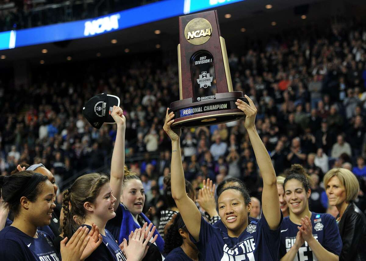 UConn senior Saniya Chong lifts the regional championship trophy after their victory over Oregon in an NCAA regional final at the Webster Bank Arena in Bridgeport on March 27, 2017.