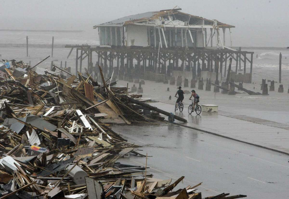 In this Sept. 14, 2008 photo, cyclists ride past debris piled up on the seawall road after Hurricane Ike hit the Texas coast in Galveston. (AP Photo/Matt Slocum, File)