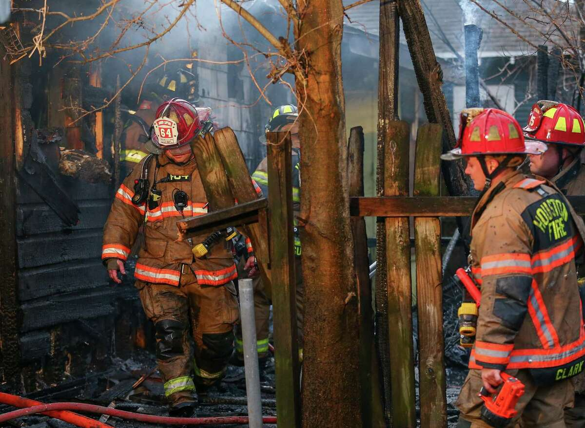 Houston firefighters wear heavy protective gear that can easily weigh 50 to 60 pounds. Modern day building materials and furnishings can emit carcinogens when they catch fire, depositing particles in firefighters' bunker gear that can only be removed with special cleaning machinery.