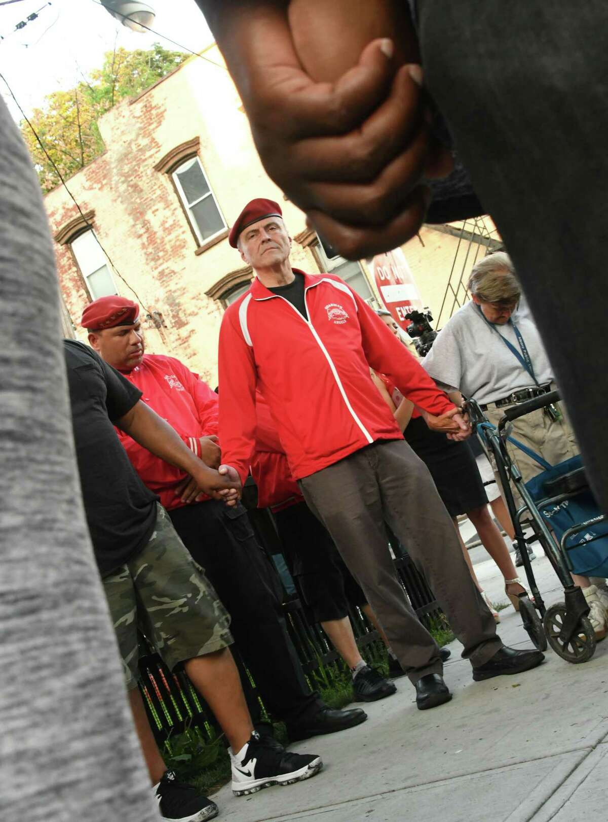 Guardian Angel Founder Curtis Sliwa, center, prays in a group per a request by a resident as people gather at the corner of Clinton and Lexington Avenues in response to the recent spate in violence on Tuesday, July 10, 2018 in Albany, N.Y. (Lori Van Buren/Times Union)