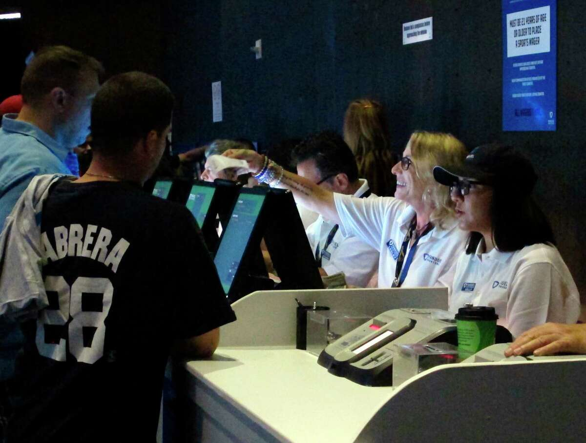 In this Saturday, July 14, 2018 photo a clerk hands a sports betting ticket to a gambler at the Meadowlands Racetrack in East Rutherford N.J., minutes after it started accepting sports bets. FanDuel Group says it plans to offer sports betting for the track, and a full internet casino operation in time for the start of football season in September. Sports betting in New Jersey began last month, generating $16.4 million in bets during its first two weeks. (AP Photo/Wayne Parry)