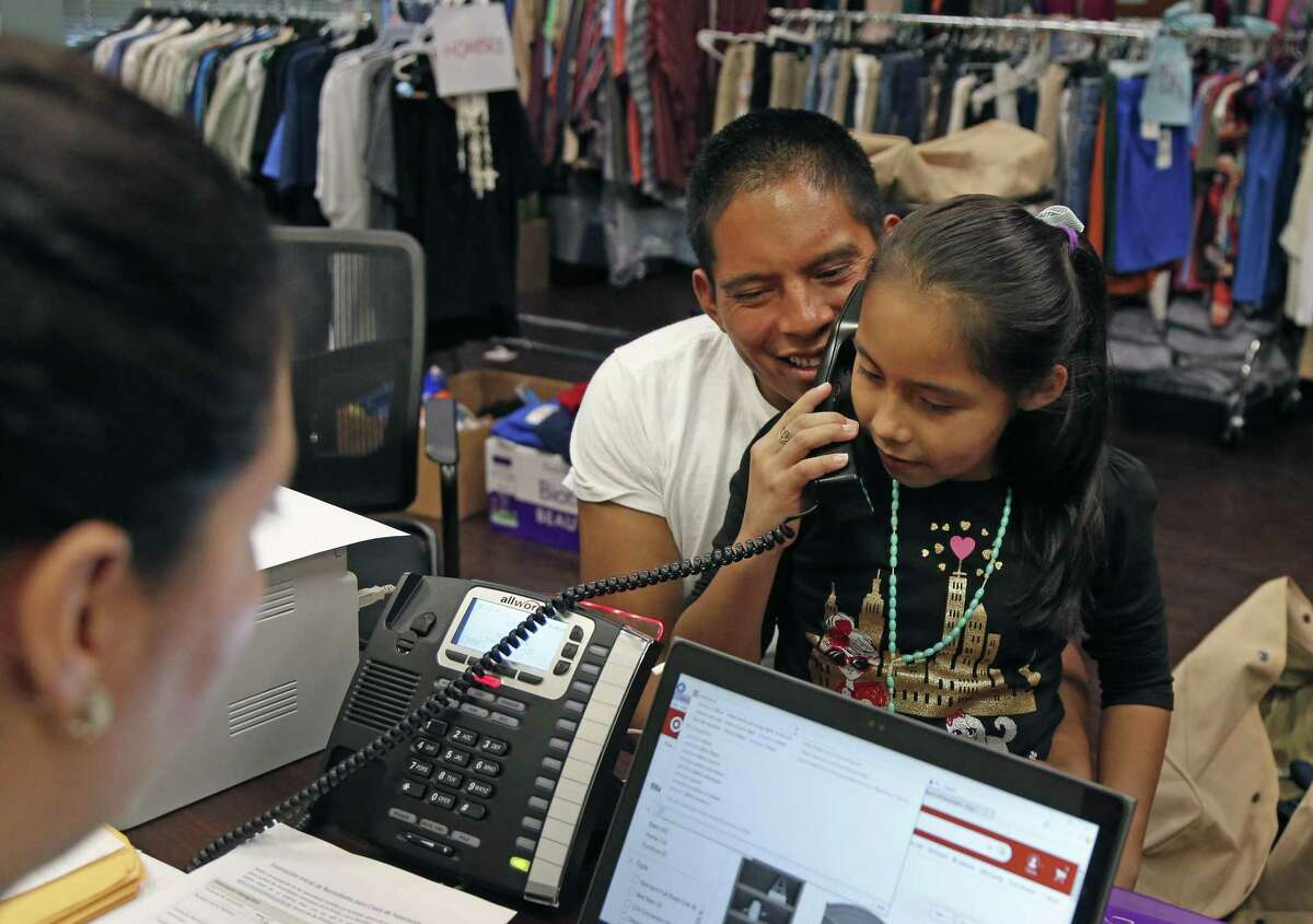 Juan Bajurto holds daughter Genesis, 9, as she talk to her aunt, Bajurto's sister, Wednesday evening after arriving at Catholic Charities in San Antonio. Bajurto and his daughter will travel to his sister's location and stay with her while waiting for their case to be heard.
