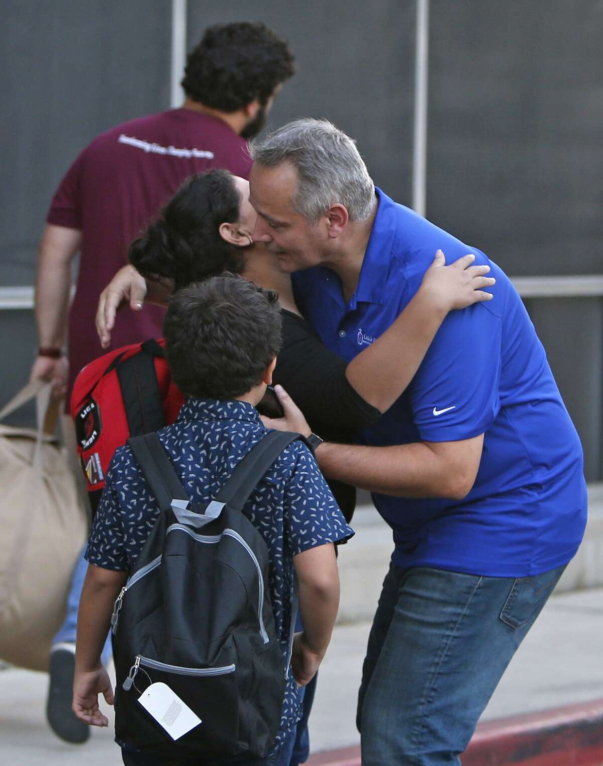 Antonio Fernández (right), head of Catholic Charities of San Antonio, says goodbye to a family of recently reunified immigrants after they were processed at Wednesday at Catholic Charities.