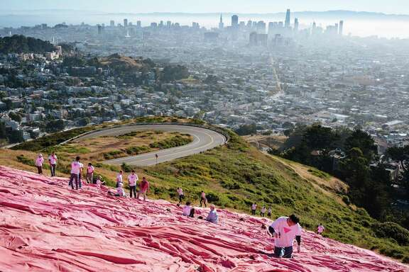 Volunteers make the finishing touches to the Pink Triangle at Twin Peaks in San Francisco on Saturday, June 23, 2018.