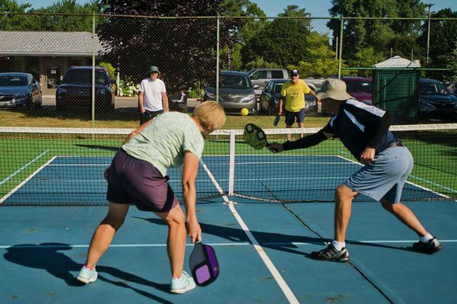 From left, Midland residents Jack Lewis, Cheryl Corbett, Steve Stackable and Wally Rhodes play a game of pickleball on one of the four pickleball courts in Central Park on Wednesday morning. (Katy Kildee/kkildee@mdn.net)
