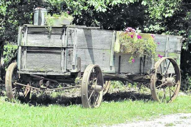 An old wagon on the side of a driveway in rural Nortonville serves as a large planter for flowers.