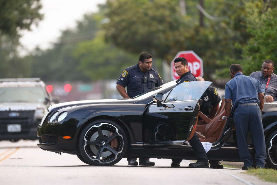Housotn Police officers investigate the scene where a man was shot on Greenridge Drive, outside of the Centerfolds gentlemen club Thursday, July 19, 2018, in Houston.