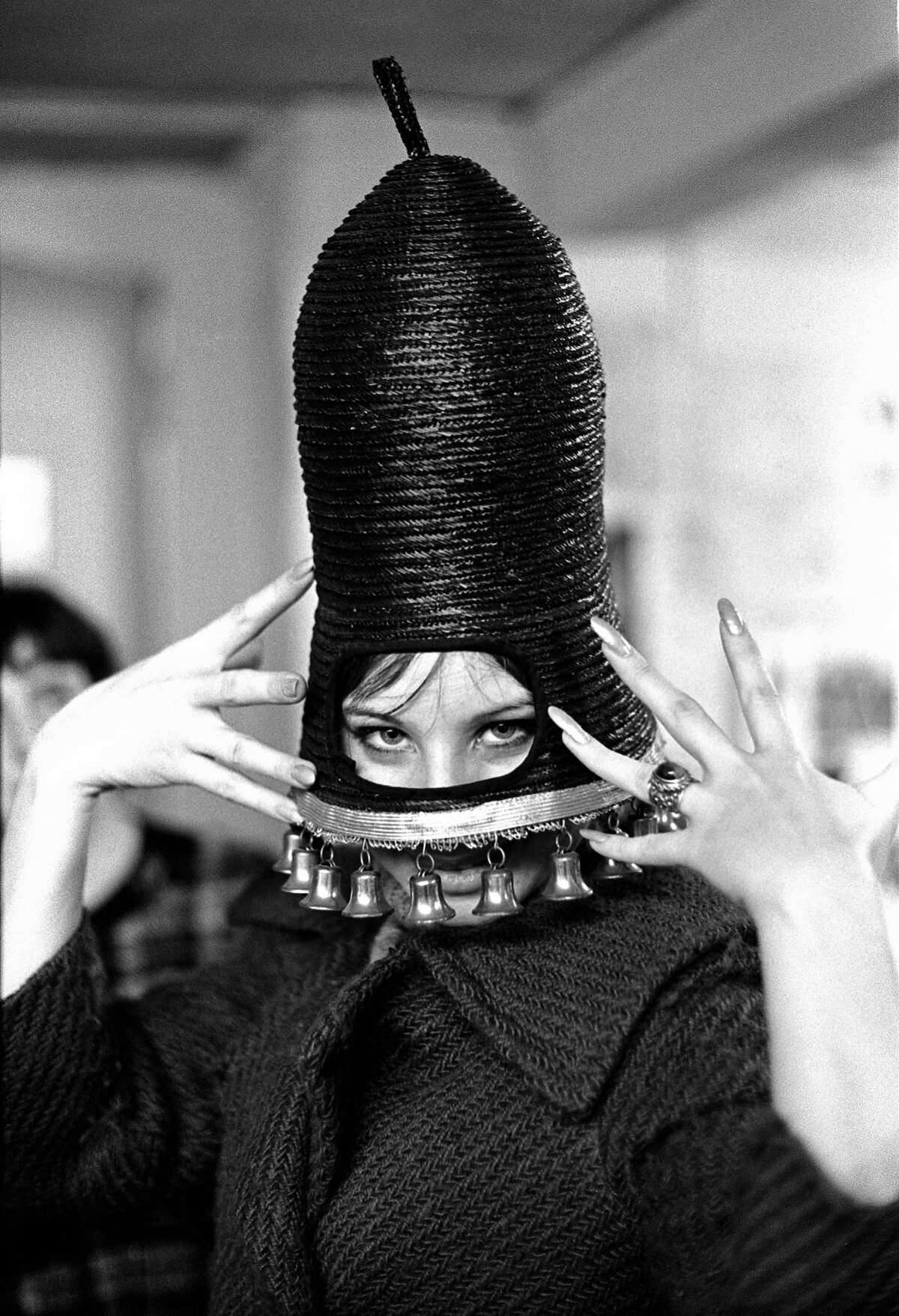 """Barbra Streisand tries on hats in a thrift shop in New York City, 1963. The shop was """"Little Nothings"""""""