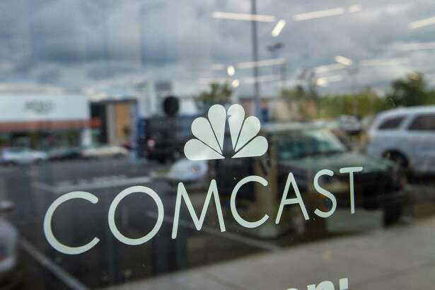 Signage is displayed in the window of a Comcast Corp. Xfinity store in King of Prussia, Pa.