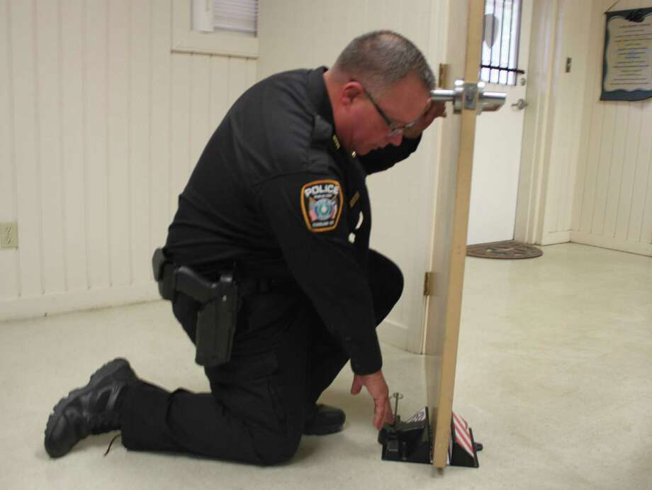 Splendora ISD Police Chief Rex Evans demonstrates how door stops can be slipped under the bottom of a door and then a pin slipped into place to prevent the door from being forced open during an active shooter situation. Photo: Vanesa Brashier / Vanesa Brashier