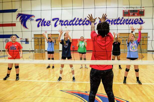 Clear Lake volleyball coach Chanda Eager instructs participants how to set the ball during the Clear Lake volleyball camp held at Krueger Field House.(Photos by ©Kim Christensen)