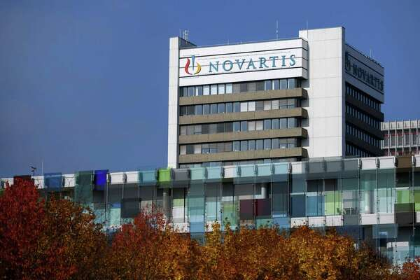 This file photograph taken on October 27, 2015, shows the logo of Swiss pharmaceutical giant Novartis on the top of a building at the company's campus in Basel. Pharmaceutical companies are scrambling to stem the groundswell of criticism over steep drug pricing. Novartis, the Swiss drugmaker, said Wednesday that it would not raise prices on its U.S. products for the rest of 2018, joining Pfizer, which delayed its increases last week after President Donald Trump singled out the company for criticism.
