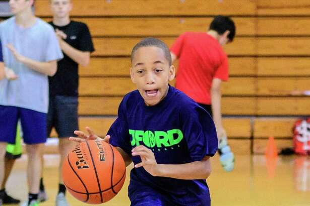 Reese Winborn, 11, works on his dribbling during the Pearland basketball camp held at Turner High School. (Photos by ©Kim Christensen)
