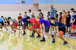 Camp participants try to dribble between their legs as assistant varsity basketball coach David Koonsen give words of encouragement during the Pearland basketball camp held at Turner High School. (Photos by ©Kim Christensen)