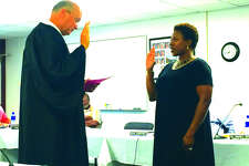 Madison County's Chief Judge David Hylla swears in the Edwardsville District 7's new board member Nekisha Omotola during the general board of education meeting Monday night. Omotola was appointed to fill the seat of William Catalano who resigned at the last board meeting.