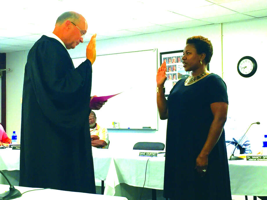 Madison County's Chief Judge David Hylla swears in the Edwardsville District 7's new board member Nekisha Omotola during the general board of education meeting Monday night. Omotola was appointed to fill the seat of William Catalano who resigned at the last board meeting. Photo: Julia Biggs/Intelligencer