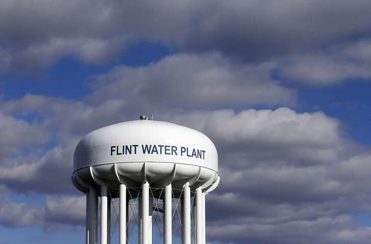 FILE - In this pMarch 21, 2016, file photo, the Flint Water Plant water tower is seen in Flint, Mich. A federal watchdog is calling on the U.S. Environmental Protection Agency to strengthen its oversight of state drinking water systems in the wake of the lead crisis in Flint, Michigan. In a report released July 19, 2018, the EPA's Office of Inspector General says the agency must act now to be able to react more quickly in times of public-health emergencies.. (AP Photo/Carlos Osorio, File)