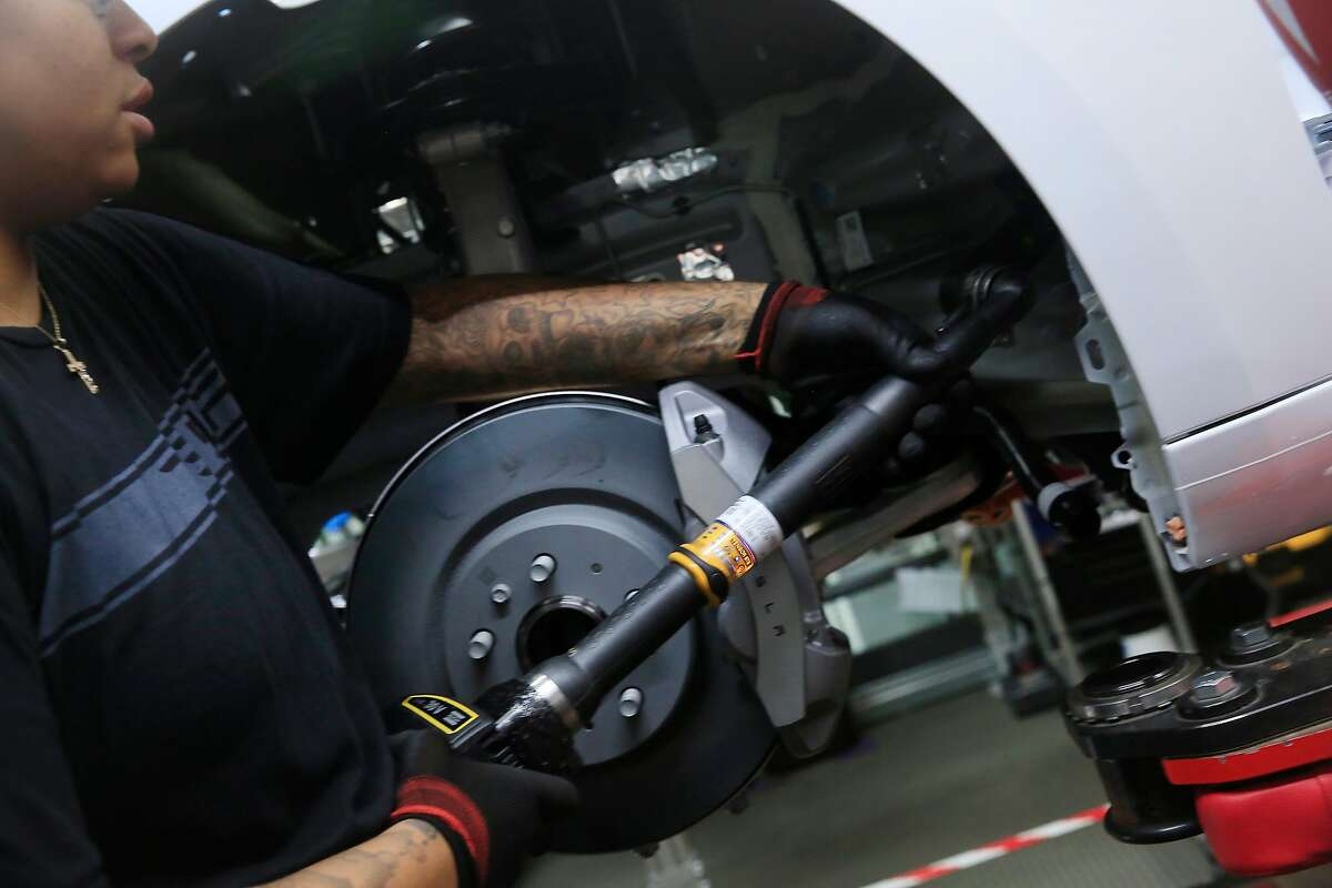 A production associate demonstrates how to use a tool while working on a Tesla Model 3 at the Tesla factory on Wednesday, July 18, 2018 in Fremont, Calif.