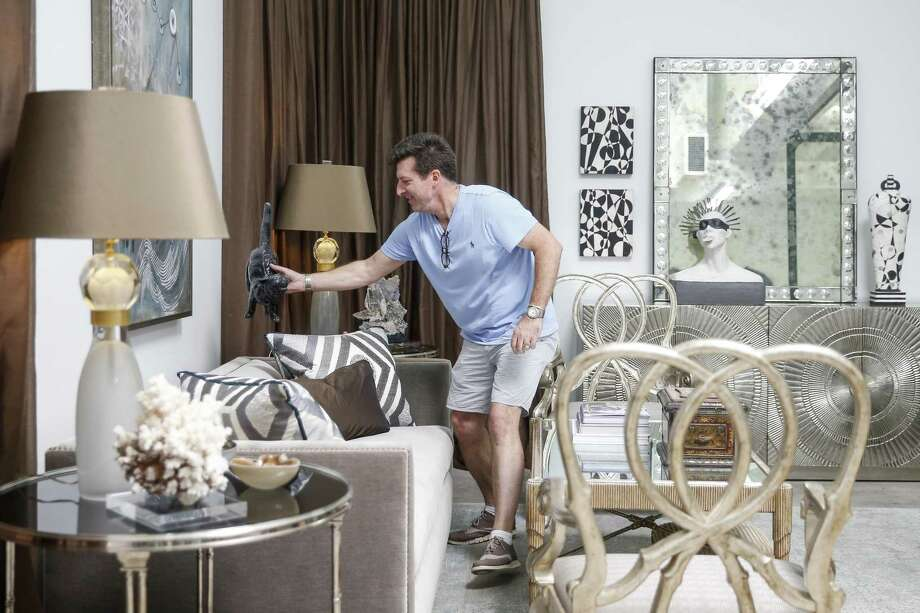 Interior designer Denny Lyons arranges decor in his bedroom space. Photo: Michael Ciaglo /Staff Photographer / Michael Ciaglo